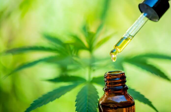 CBD Oil Bottle Besides Hemp Leaf